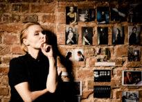 Ceglana ściana obklejona zdjęciami. Przy niej bokiem stoi kobieta ubrana na czarno o blond włosach. Trzyma palec przy ustach, sugerując ciszę. Na zdjęciu Ewa Szumska.