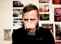 Mężczyzna o krótki włosach stoi na tle białej ściany na której wiszą zdjęcia. Przysłania sobie twarz ręką, którą pokazuje środkowy palec. Ubrany jest na czarno. Na zdjęciu Jakub Papuga.