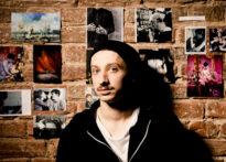 Mężczyzna w czarnej czapce z wąsem opiera się o ceglaną ścianę, na której wiszą zdjęcia. Na zdjęciu Konrad Cichoń.