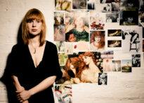 Rudowłosa kobieta opiera się plecami o ścianę, na której wiszą zdjęcia. Jej ubranie jest czarne, a ściana biała. Na zdjęciu: Kornelia Trawkowska.