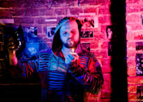 Mężczyzna z zarostem ubrany w kolorową kurtkę stoi na tle ceglanej ściany obwieszonej zdjęciami. Pada na niego różowe światło. W ręku trzyma zapaloną zapalniczkę. a w ustach papierosa. Na zdjęciu Mariusz Adamski.