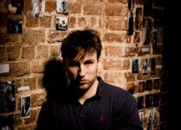 Mężczyzna o krótkich ciemnych włosach opiera się o ceglaną ścianę, wokół niego fotografie. Ubrany jest w czarny krótki rękaw. Na zdjęciu Mateusz Wiśniewski.