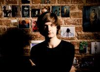 Ceglana ściana obklejona zdjęciami. Mężczyzna ma brązowe włosy i czarne ubranie. Wpatruje się w obiektyw. Na zdjęciu: Michał Sikorski.