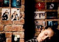 Ceglana ściana obklejona zdjęciami. Dziewczyna o brązowych włosach pochyla głowę w bok, oczy ma zamknięte. Na zdjęciu: Monika Roszko.