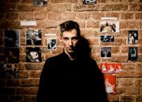 Mężczyzna stoi na tle ceglanej ściany obwieszonej zdjęciami. Wpatruje się w obiektyw i jest ubrany na czarno. Na zdjęciu: Paweł Siwiak.