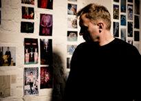 Na białej ścianie wiszą kolorowe zdjęcia. Na jej tle stoi mężczyzna w czarnym swetrze z zacienioną twarzą.