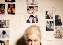 Biała ściana obwieszona zdjęciami. Na dole fotografii widać blondwłosą kobietę z włosami zebranymi w kok, która wpatruje się zawzięcie w obiektyw. Na zdjęciu Teresa Kwiatkowska.