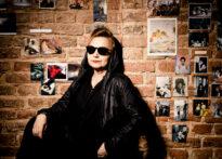 Ceglana ściana obwieszona zdjęciami. Na jej tle stoi kobieta ubrana na czarno, z kapturem na głowie i w okularach przeciwsłonecznych. Ma usta pomalowane na czerwono. Opiera rękę na kolanie. Na zdjęciu Barbara Krasińska.