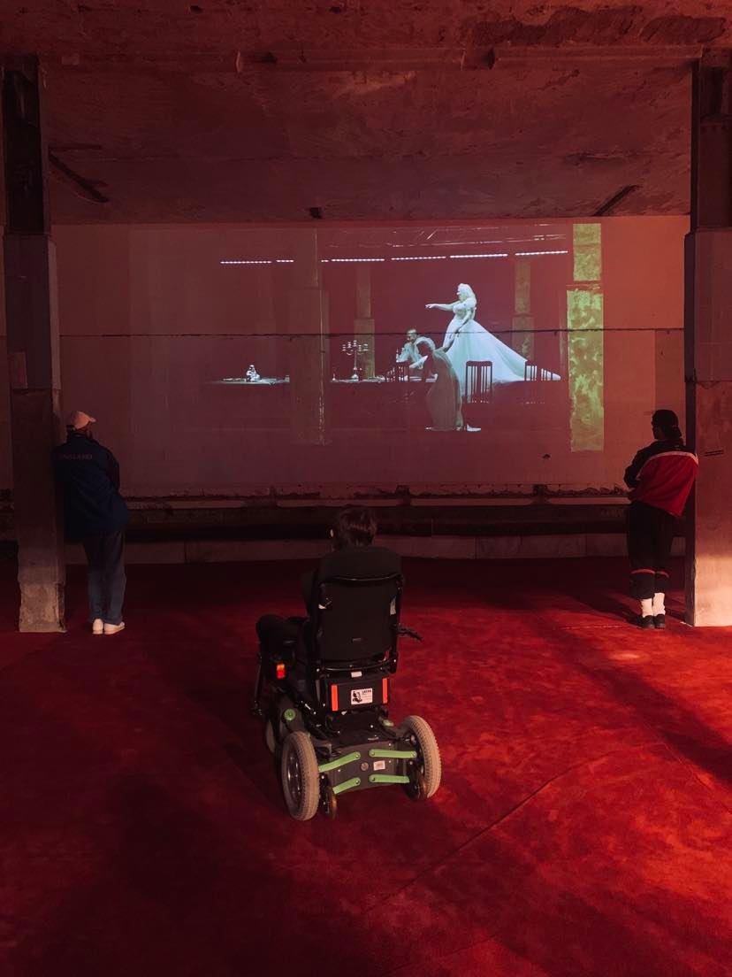Widziany od tyłu wózek inwalidzki stojący na czerwonym dywanie. W tle na ścianie widać projekcję ze spektaklu.