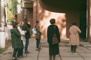 Grupa osób wkurtkach isłuchawkach stoi nachodniku przedbrązowym budynkiem iwpatruje się wniego, zasłuchana. Widać, żejest tosłoneczny dzień.