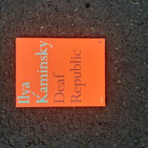 """Pomarańczowa okładka książki znapisem """"Ilya Kaminsky Deaf Republic""""."""