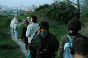 Grupa osób ubranych wkurtki iczapki wędruje polną ściężką. Wszyscy mają założone słuchawki. Wokół nich rośnie trawa. Woddali widać rozmazane budynki iświatła miasta.