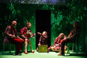 Pięć osób odzianych wkolorowe, ludowe stroje siedzi, część nakrzesłach aczęść napodłodze. Jedna zkobiet siedzących nakrzesłach trzyma wdłoniach bukiet kwiatów. Scena skąpana jest wzielonym świetle.
