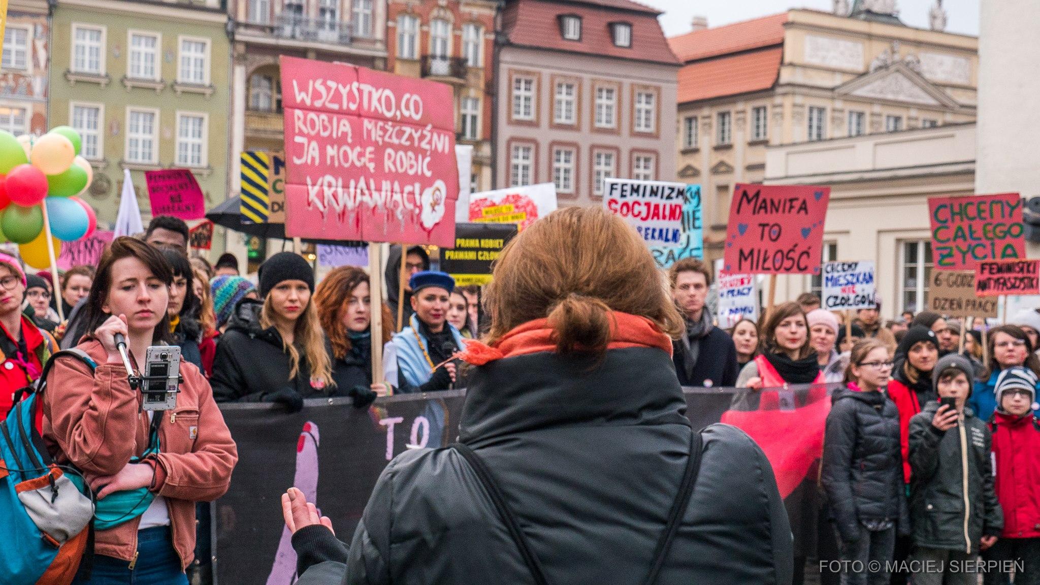 """Zdjęcie z protestu. Kobiety ubrane w kurtki stoją obok siebie z transparentami i plakatami. Na jednym z nich napisane jest """"Wszystko, co robią mężczyźni ja mogę robić krwawiąc!""""."""
