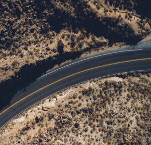 Zrobione zdużej wysokości zdjęcie asfaltowej drogi, któralekko zakręca. Poobu jej stronach widać piaszczysty teraz, porośnięty roślinnością.