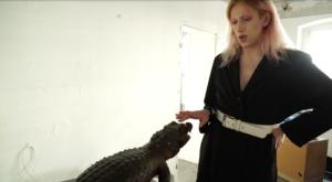 Osoba odługich blond włosach ubrana wczarną sukienkę przepasaną białym paskiem stoi wbiałym pokoju. Trzyma dłoń nadgłową krokodyla.