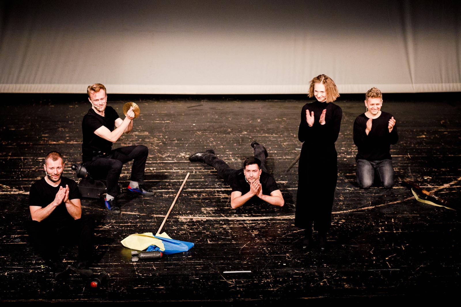 5 osób ubranych na czarno stoi lub leży na nagich deskach sceny.