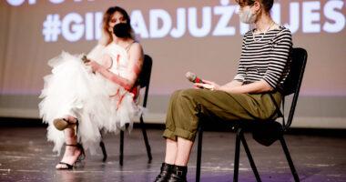 Dwie osoby siedzą na scenie na krzesłach. Jedna ma długie włosy, białą sukienkę i szpilki, a druga bluzkę i spodnie. Obie osoby mają długie włosy.