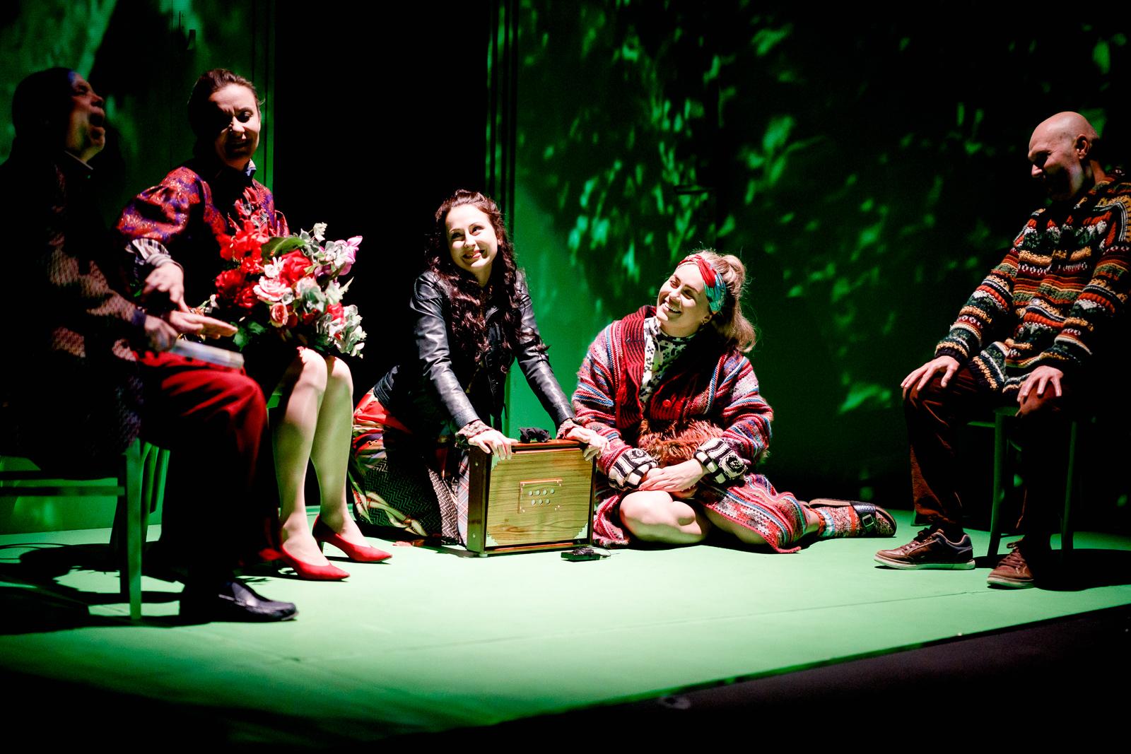 Pięć osób w kolorowych ubraniach siedzi na krzesłach i zielonej podłodze. Większość z nich znajduje się w półcieniu.