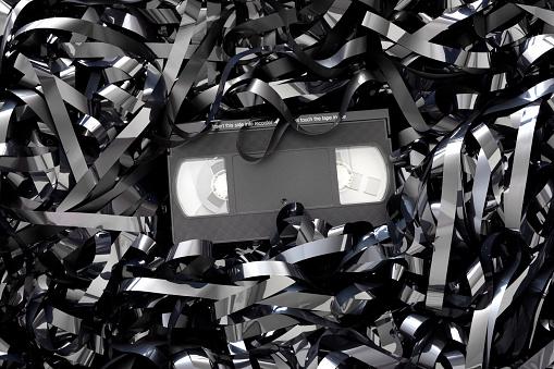 Czarno-białe zdjęcie kasety, z której wychodzi taśma.