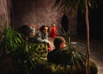 Zdjęcie pokoju. Na pierwszym planie rozłożyste rośliny. Przy nich na kanapie siedzą Don Juan i Sganarel. Na dalszym planie przy ścianie siedzi Donna Elwira.