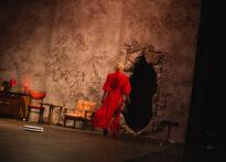 Zdjęcie przedstawia widzianą z tyłu sylwetkę Don Elwiry odzianej w czerwoną suknię, która wędruje w stronę dziury w ścianie.