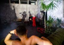 Zdjęcie pomieszczenia. Na pierwszym planie widać rozmazane plecy i tył głowy Don Juana. W dalszym tle postacie rzucają cienie na ścianę.