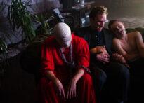 Na zdjęciu trzy osoby siedzące na kanapie. Pierwsza z lewej ubrana jest na czerwono i ma twarz zasłoniętą workiem. Obok niej siedzi dwóch mężczyzn (Don Carlos/Don Alonzo i Don Juan).