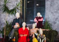 Fotografia ze spektaklu, na której postacie wyglądają jak na zdjęciu rodzinnym, usadzone na kanapie i wokół niej. Jednak wszyscy mają na głowach worki i nie widać ich twarzy.