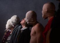 Rząd stojących obok siebie postaci. Każda z nich ma na głowie worek który zasłania ich całe twarze poza Posągiem Komandora, który stoi na środku.
