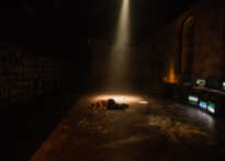 Zdjęcie ze spektaklu. Szerokie ujęcie pomieszczenia. Na samym środku na ziemi leży nieruchoma postać Don Juana. Pada na niego wąski promień światła. Reszta pomieszczenia jest zacieniona.