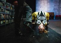 Na zdjęciu widok z pozycji podłogi. Kobieta w ciąży (Małgośka) wygięta nienaturalnie na krześle w pozycji, w której jej głowa dotyka ziemi. Obok niej widać drugą postać od pasa w dół, w szerokich szarych spodniach i eleganckich czarnych butach.