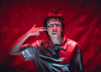 Na zdjęciu mężczyzna w srebrnym kostiumie na tle czerwonej tkaniny. Trzyma dwa palce przy głowie jak do strzału. Ma srebrną farbę wokół oczu.