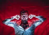 Mężczyzna z zarostem i nosem pomalowanym na srebrno stoi na tle czerwonej tkaniny. Ma skrzywioną minę, przy twarzy trzyma ugięte pięści. Jest ubrany na srebrno.