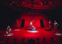 Zdjęcie zrobione z dużej odległości. Scena skąpana w czerwonym świetle, a na niej 5 osób w metalicznie srebrnych kostiumach.