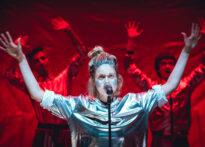 Kobieta w srebrnym kostiumie stoi przed mikrofonem z rozpostartymi ramionami. Za nią widać dwóch mężczyzn oświetlonych na czerwono z rękami w górze.
