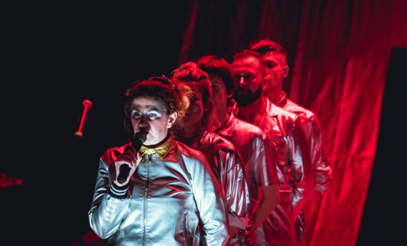 Wszystkie postacie stoją w rzędzie jedna za drugą. Na przedzie rzędu stoi kobieta w srebrnym stroju mówiąca do mikrofonu. Na resztę rzędu pada czerwone światło.