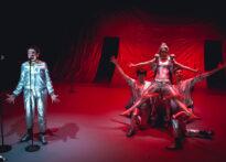 Po lewej stronie zdjęcia kobieta stoi przed mikrofonem i mówi. Po prawej trzech mężczyzn trzyma kobietę w powietrzu. Ona ma szeroko rozłożone nogi i ręce. Wszystkie postacie są ubrane na srebrno i pada na nie czerwone światło.