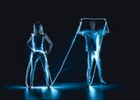 Kobieta i mężczyzna w lśniących, srebrnych kostiumch owijają się sznurem białych lampek. Wokół nich jest ciemno, widać tylko światło lampek odbijające się od srebrnych ubrań.