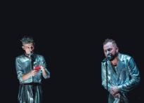 Dwóch mężczyzn w srebrnych kostiumach mówi do mikrofonów. Jeden z nich trzyma telefon.